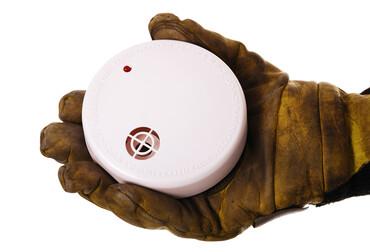 Rookmelder in hand van brandweerman